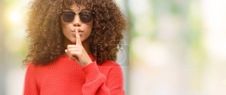 Photo pour Femme afro-américaine portant des lunettes de soleil avec index sur les lèvres, demandez à se taire. Silence et concept secret - image libre de droit