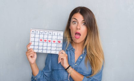 Young adult woman over grey grunge wall showing period calendar scared in shock with a surprise face, afraid and excited with fear expression
