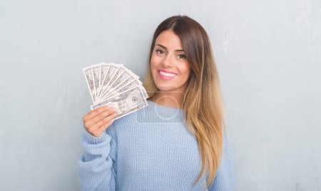 Young adult woman over grey grunge wall holding dollars with a happy face standing and smiling with a confident smile showing teeth