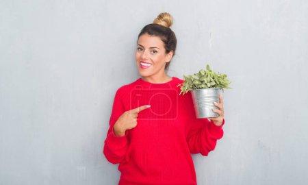 Photo pour Jeune femme adulte au-dessus du mur gris grunge comprenant plante plot montrant très heureux avec la main et des doigts - image libre de droit