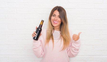 Photo pour Femme adulte Yound sur mur de briques blanches comprenant bière pointant et montrant avec le pouce jusqu'à la face visage heureux souriant - image libre de droit