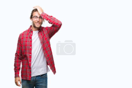Young handsome man with long hair wearing glasses over isolated background surprised with hand on head for mistake, remember error. Forgot, bad memory concept.