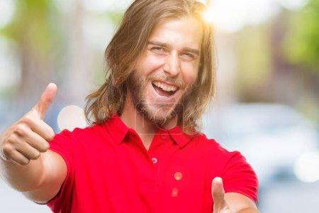 Photo pour Jeune homme beau aux cheveux longs sur fond isolé approuvant faire un geste positif avec la main, le pouce levé souriant et heureux pour le succès. En regardant la caméra, geste gagnant . - image libre de droit