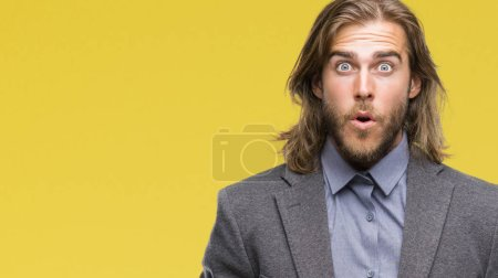 Young handsome business man with long hair over isolated background afraid and shocked with surprise expression, fear and excited face.