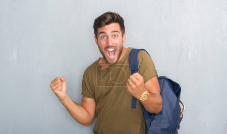 Handsome tourist young man over grey grunge wall wearing backpack celebrating surprised and amazed for success with arms raised and open eyes. Winner concept.