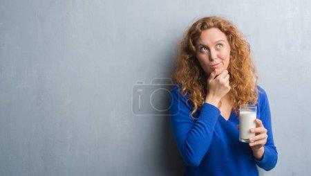 Photo pour Jeune rousse femme boire un verre de lait visage sérieux en pensant à la question, idée très confuse - image libre de droit