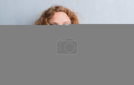 Photo pour Femme médecin jeune rousse au fil du mur gris grunge comprenant une pilule sérieux face à réfléchir à la question, idée très confuse - image libre de droit