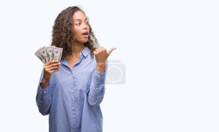 Photo pour Jeune femme hisoire holding dollars pointant et montrant avec le pouce jusqu'à la face visage heureux souriant - image libre de droit