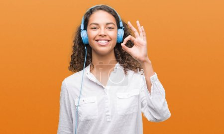 Young hispanic woman wearing headphones doing ok sign with fingers, excellent symbol