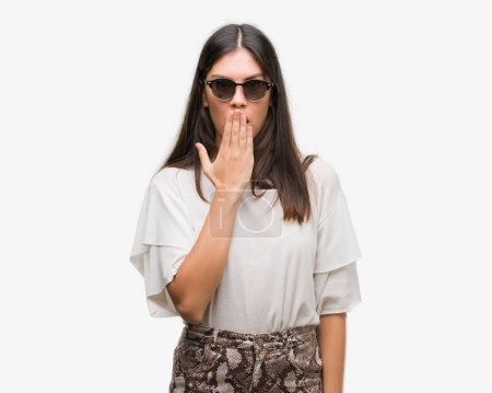 Young beautiful hispanic wearing sunglasses cover mouth with hand shocked with shame for mistake, expression of fear, scared in silence, secret concept