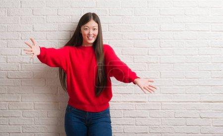 Photo pour Jeune femme chinoise au-dessus du mur de briques regardant la caméra souriant à bras ouverts pour un câlin. Expression joyeuse embrassant le bonheur . - image libre de droit