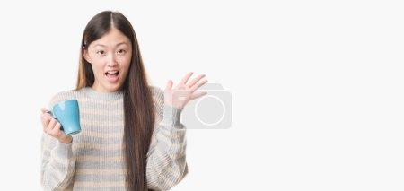 Photo pour Jeune femme chinoise sur fond isolé driking tasse de café très heureux et excité, expression gagnante célébrant la victoire en criant avec un grand sourire et les mains levées - image libre de droit