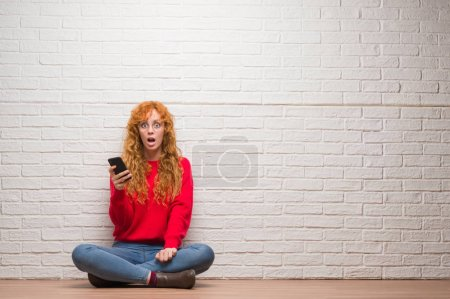 Young redhead woman sitting over brick wall talking on the phone scared in shock with a surprise face, afraid and excited with fear expression