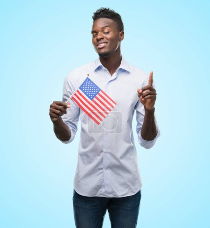 Photo for Young african american man holding USA flag surprised with an idea or question pointing finger with happy face, number one - Royalty Free Image