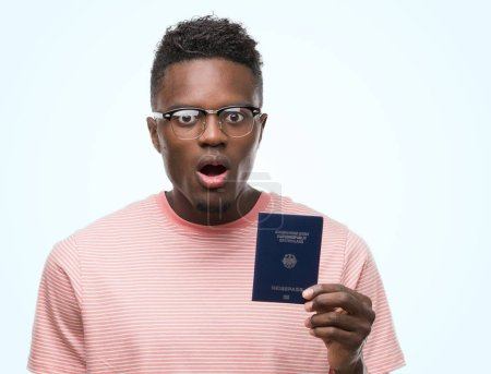 Young african american man holding german passport scared in shock with a surprise face, afraid and excited with fear expression