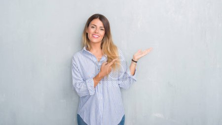 Photo for Young adult woman over grey grunge wall wearing fashion business outfit amazed and smiling to the camera while presenting with hand and pointing with finger. - Royalty Free Image