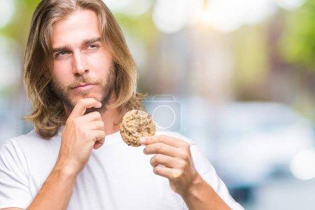 Photo pour Jeune homme beau aux cheveux longs mangeant du chocolat sur fond isolé visage sérieux réfléchissant à la question, idée très confuse - image libre de droit