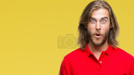 Young handsome man with long hair over isolated background afraid and shocked with surprise expression, fear and excited face.