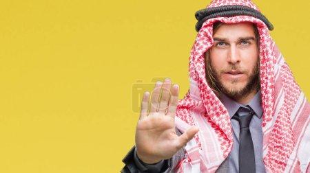 Photo pour Jeune bel homme arabe aux cheveux longs portant keffieh sur fond isolé faisant escale chanter avec la paume de la main. Expression d'avertissement avec un geste négatif et sérieux sur le visage - image libre de droit