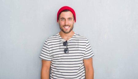 Foto de Hombre guapo joven inconformista sobre pared gris grunge con camiseta azul marino y gorra de lana con una sonrisa feliz y fresca en la cara. Afortunado. - Imagen libre de derechos