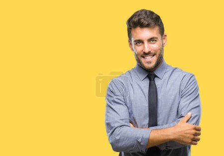 Young handsome business man over isolated background happy face smiling with crossed arms looking at the camera. Positive person.