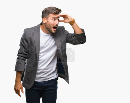 Young handsome business man over isolated background very happy and smiling looking far away with hand over head. Searching concept.