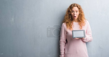 Young redhead woman over grey grunge wall using tablet scared in shock with a surprise face, afraid and excited with fear expression