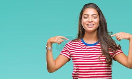 Foto de Joven hermosa mujer árabe sobre fondo aislado mirando seguros con sonrisa en la cara, uno apuntando con los dedos felices y orgullosos. - Imagen libre de derechos