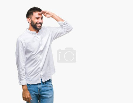 Adult hispanic man over isolated background very happy and smiling looking far away with hand over head. Searching concept.