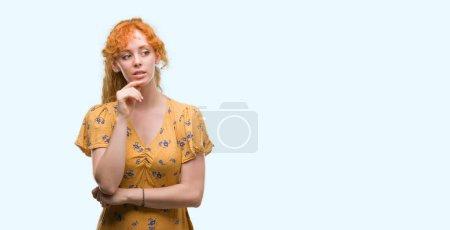 Photo pour Jeune femme rousse avec la main sur le menton penser à la question, expression coûteuse. Souriant avec un visage réfléchi. Concept de doute . - image libre de droit
