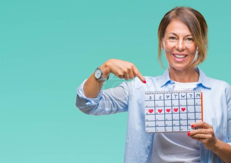 Photo for Middle age senior hispanic woman holding menstruation calendar over isolated background very happy pointing with hand and finger - Royalty Free Image
