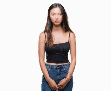 Photo pour Jeune femme asiatique sur fond isolé avec une expression sérieuse sur le visage. Un regard simple et naturel sur la caméra . - image libre de droit
