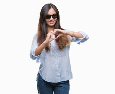 Young asian woman wearing sunglasses over isolated background smiling in love showing heart symbol and shape with hands. Romantic concept.