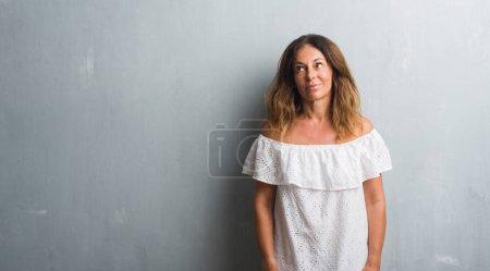 Photo pour Moyen Age femme hispanique debout sur le mur gris grunge souriant côté regardant et regardant loin en pensant . - image libre de droit