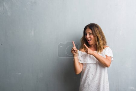 Photo for Middle age hispanic woman standing over grey grunge wall smiling and looking at the camera pointing with two hands and fingers to the side. - Royalty Free Image