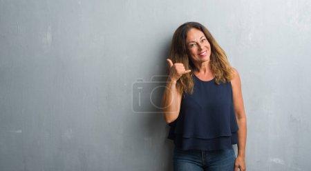 Photo pour Femme hispanique du Moyen Âge debout sur le mur gris grunge souriant faire geste de téléphone avec la main et les doigts comme parler au téléphone. Communication des concepts . - image libre de droit