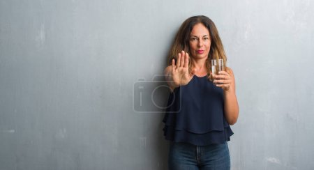 Middle age hispanic woman drinking glass of water with open hand doing stop sign with serious and confident expression, defense gesture