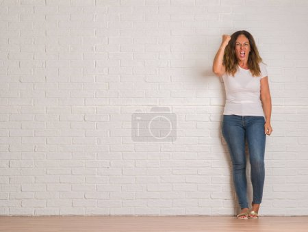 Middle age hispanic woman standing over white brick wall annoyed and frustrated shouting with anger, crazy and yelling with raised hand, anger concept