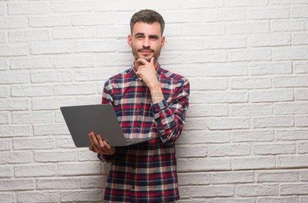 Photo pour Jeune homme adulte sur le mur de briques en utilisant un ordinateur portable visage sérieux en pensant à la question, idée très confuse - image libre de droit