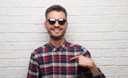 Photo pour Jeune homme adulte portant des lunettes de soleil debout sur un mur de briques blanches avec un visage surprise pointant du doigt vers lui-même - image libre de droit