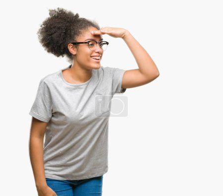 Young afro american woman wearing glasses over isolated background very happy and smiling looking far away with hand over head. Searching concept.