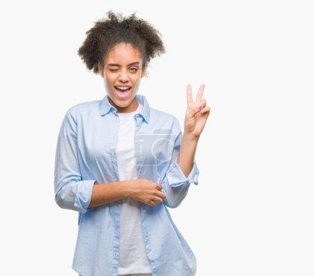 Mujer afroamericana joven sobre fondo aislado sonriendo con la cara feliz guiñando el ojo a la cámara haciendo signo de victoria. Número dos. .