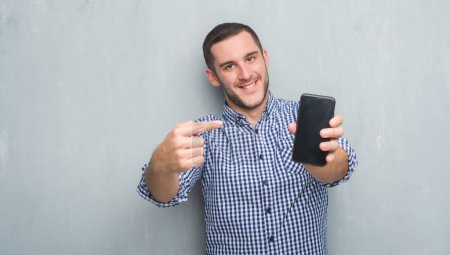 Photo for Young caucasian man over grey grunge wall showing blank screen of smartphone very happy pointing with hand and finger - Royalty Free Image