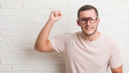 Young caucasian man standing over white brick wall wearing glasses annoyed and frustrated shouting with anger, crazy and yelling with raised hand, anger concept