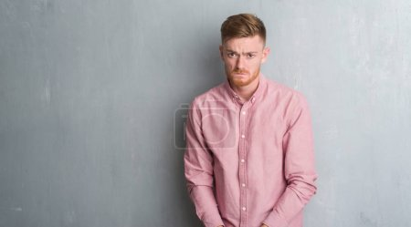 Photo for Young redhead man over grey grunge wall wearing pink shirt depressed and worry for distress, crying angry and afraid. Sad expression. - Royalty Free Image