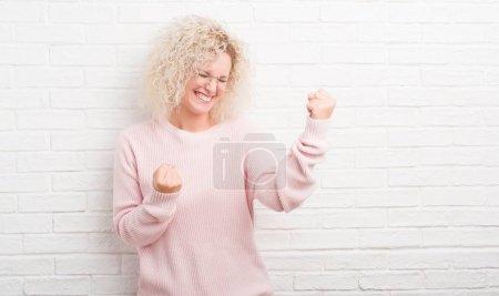 Photo pour Jeune femme blonde aux cheveux bouclés sur un mur de briques blanches très heureuse et excitée faisant geste gagnant avec les bras levés, souriant et criant pour le succès. Concept de célébration . - image libre de droit