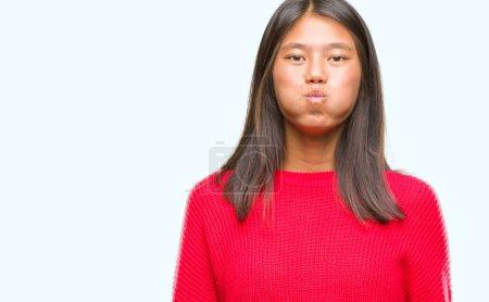 Photo pour Jeune femme asiatique portant un pull d'hiver sur fond isolé joues gonflées avec un visage drôle. Bouche gonflée avec de l'air, expression folle . - image libre de droit