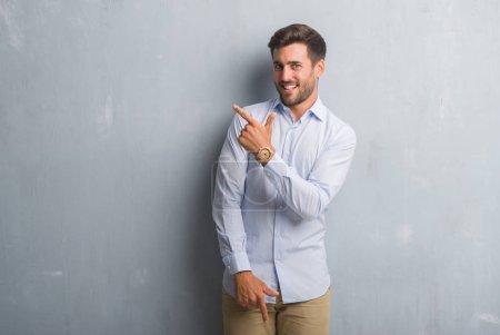 Photo pour Beau jeune homme d'affaires sur le mur gris grunge portant chemise élégante gaie avec un sourire du visage pointant avec la main et le doigt sur le côté avec une expression heureuse et naturelle sur le visage regardant la caméra . - image libre de droit