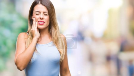 Young beautiful elegant business woman over isolated background touching mouth with hand with painful expression because of toothache or dental illness on teeth. Dentist concept.