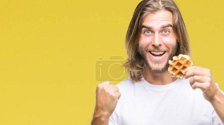 Photo pour Jeune homme beau aux cheveux longs sur fond isolé mangeant gaufre criant fier et célébrant la victoire et le succès très excité, acclamant l'émotion - image libre de droit